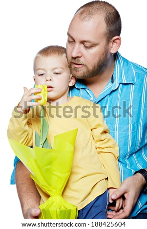Bright studio portrait of young modern father and his small son with yellow tulips on isolated white background - stock photo