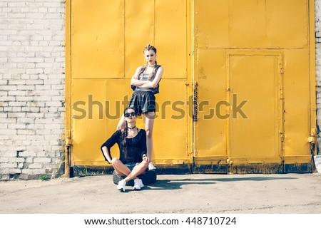 Bright stylish lifestyle outdoor portrait of two pretty best friends girls posing at street. Urban scene