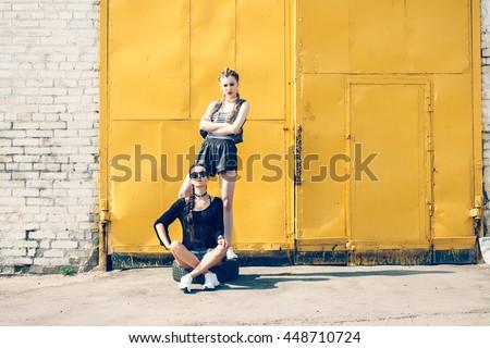 Bright stylish lifestyle outdoor portrait of two pretty best friends girls posing at street. Urban scene - stock photo