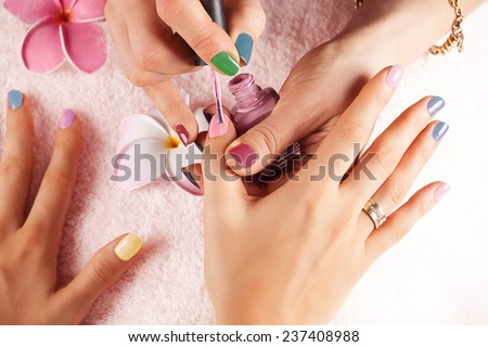 Bright stylish manicure with colored nail. Manicure process close up. Beauty treatment. Nail salon. - stock photo