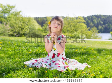 bright summer portrait of small adorable blond girl sitting on green lawn in multicolored drew with yellow dandelion