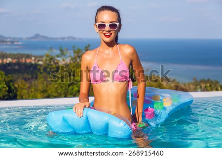 Bright summer portrait of young sexy  woman with perfect tanned slim body, wearing bikini having fun on her vacation pool party, at amazing island, view to the blue clear ocean. - stock photo