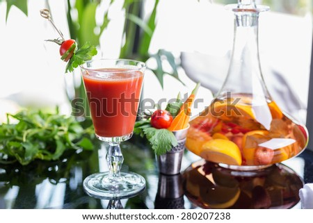 bright summer refreshing alcoholic cocktail Bloody Mary on a table in a restaurant with a creative decoration of cherry pepper greens. soft focus - stock photo