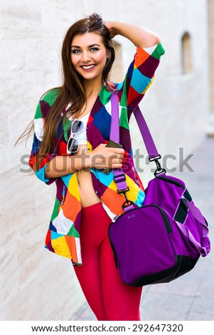 Bright summer trendy portrait of young fit girl walking on the street, wearing vivid shirt crop top and leg gins holding big sportive bag, long hairs and make up. - stock photo