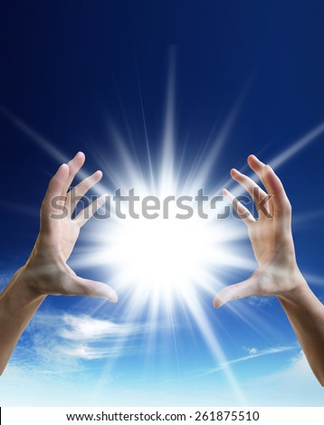 Bright sun between two hands over blue sky - stock photo