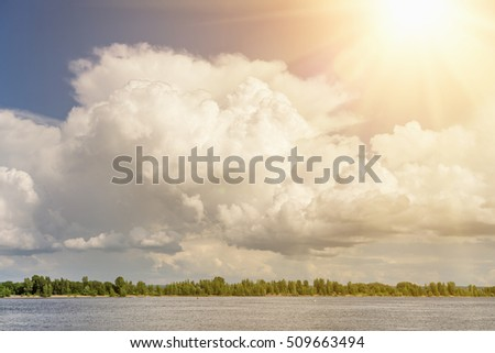 Bright sun on blue sky with white fluffy clouds, background
