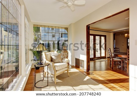 Bright sun room in soft ivory with antique chair and and small table - stock photo