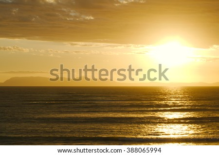 Bright sun set over ocean and mountains - stock photo