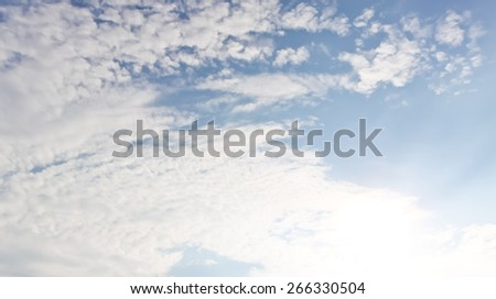 Bright sunburst with natural blue sky with fluffy white clouds soft focus. - stock photo
