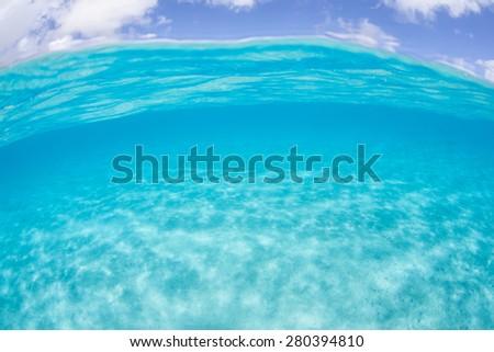Bright sunlight illuminates a shallow sandy seafloor in French Polynesia. - stock photo