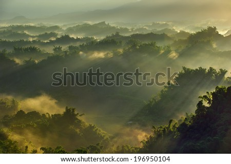 Bright sunlight streaming over numerous mountains and forests.