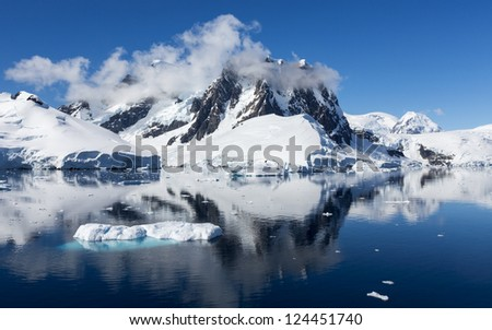 Bright sunny day in Antarctica. Full calm and reflection of icebergs in deep clear water. Travel by the ship among ices. Snow and ices of the Antarctic islands.