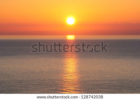 Bright sunrise under the sea surface with yellow red gradient colors - stock photo