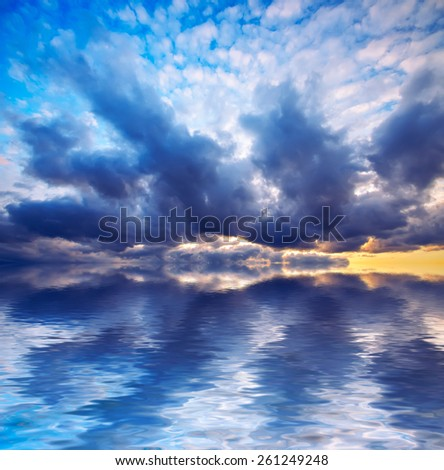 bright sunset and dramatic clouds at calm sea background. Natural composition - stock photo