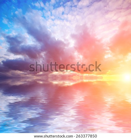 bright sunset and dramatic clouds with sun at calm sea background. Natural composition - stock photo