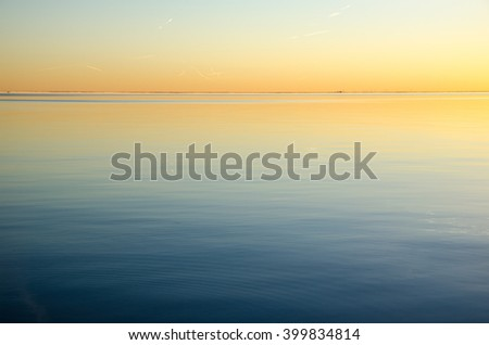 Bright sunset colors in the sky and in the calm smooth water - stock photo