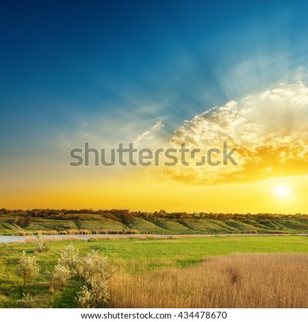 bright sunset over river and green sides of it - stock photo