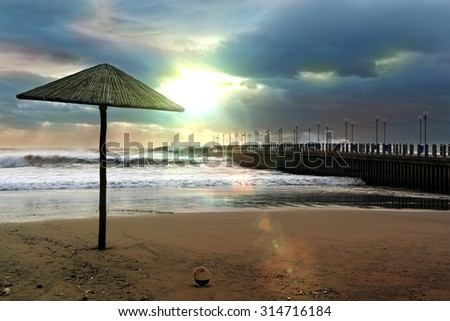 bright sunset through dense clouds on Durban Beach South Africa next to the pier - stock photo