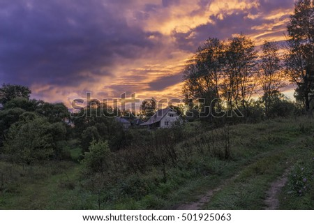 Bright sunset with dramatic cloudscape over village houses in backlit. Bulatovo village, Kaluzskaya region, Russia.