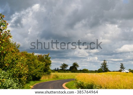 Bright sunshine and big rain clouds over the road in Denmark - stock photo