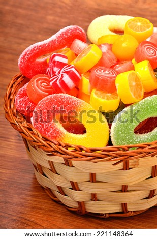 Bright sweets, lollipops, jellies in the wicker basket on the wooden background - stock photo
