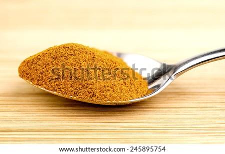 Bright turmeric powder in teaspoon - stock photo
