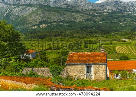 Bright valley in the mountains. The house is bright with tiled roof in a green valley. Bright big clouds over the mountains. Lonely house in the valley in the mountains. Bright summer landscape.