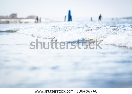 Bright & Vibrant Shoreline Waves Crashing On The Coronado Coast With Surfers Surfing, People Standing, & The Shore In The Background - stock photo