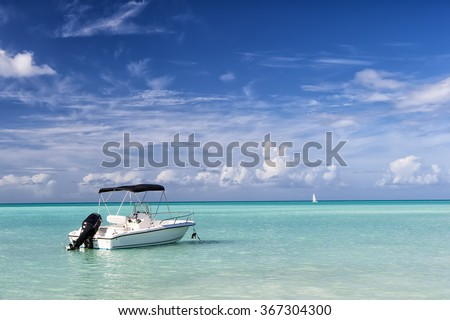 Bright view of exotic colorful beautiful marine beach of Antigua St. Johns with one wave runner on blue water and sky with small clouds in sunny weather outdoor on natural background, horizontal