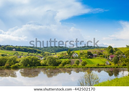 Bright view of summer nature with sunshine weather. Reflaction of trees in the river's water. Houses and mountains in the distance