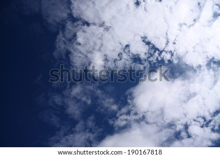 Bright white clouds in a blue sky. Taken from the ground, looking up, in the UK. - stock photo
