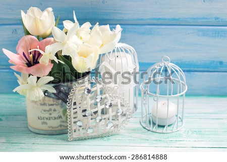 Bright white daffodils and tulips  flowers, candle on turquoise  painted wooden planks against blue wall. Selective focus. Place for text. Toned image. - stock photo