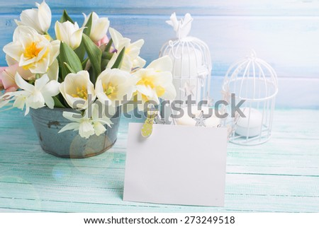Bright white daffodils and tulips  flowers in bucket, candles and  empty tag  in ray of light on turquoise  painted wooden planks against blue wall. Selective focus. Place for text.  - stock photo