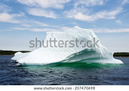 Bright white iceberg on dark water and rock background