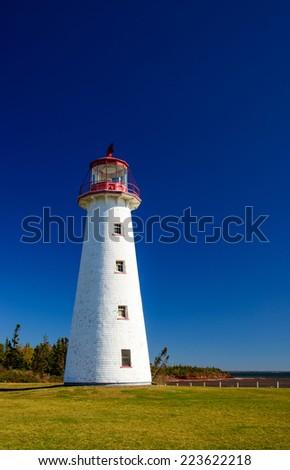Bright White Lighthouse against deep blue sky - stock photo