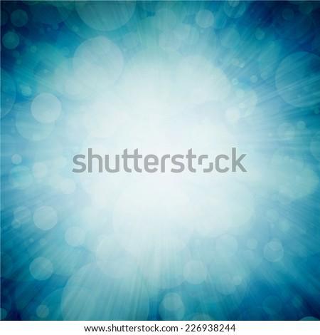 bright white sunburst design on teal blue sunburst pattern background with white bokeh lights, zoomed in effect border - stock photo