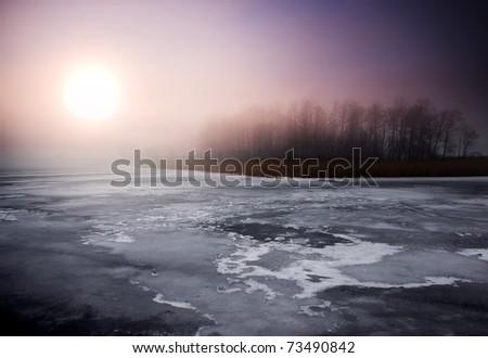 Bright winter landscape. Frozen lake and sunset - stock photo