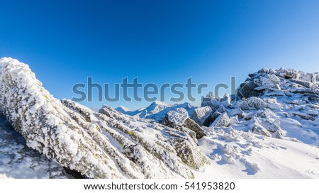 Bright winter scenery in the mountains, with frost and rocks covered with fresh snow