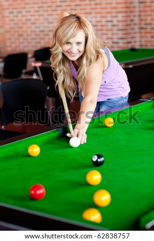 Bright woman playing pool in a club - stock photo
