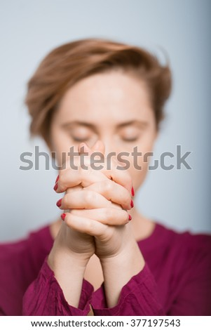 bright woman praying with her hands folded isolated studio