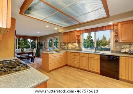 Bright wooden kitchen interior with skylight and hardwood floor. Dining room view. Northwest, USA