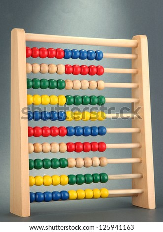Bright wooden toy abacus, on grey background