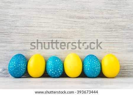 Bright yellow and blue Easter eggs on white wooden background. Copy space. - stock photo