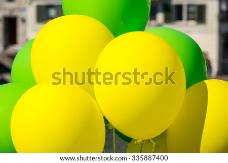 Bright yellow and green balloons on a city street event in summer. Close up shot - stock photo