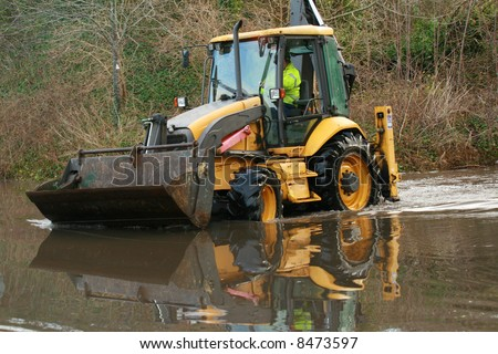 Bright yellow backhoe being driven in flood water