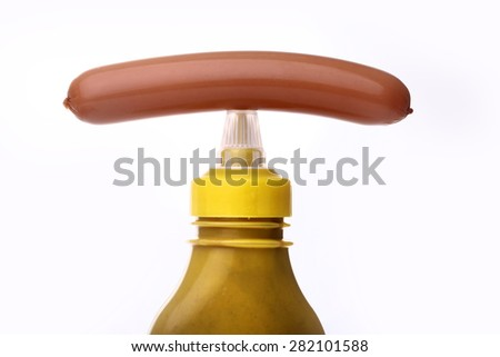 Bright yellow bottle of mustard with one frankfurter on it on a white background closeup, horizontal photo - stock photo