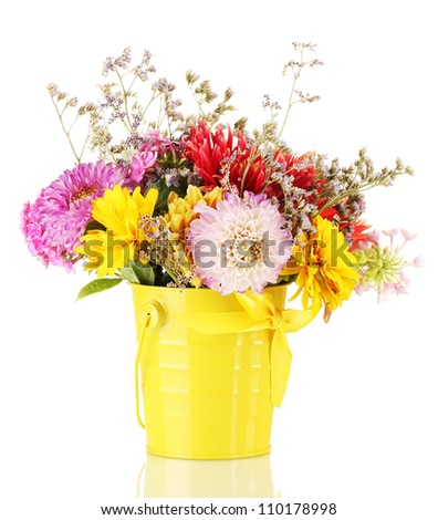 Bright yellow bucket with flowers isolated on white - stock photo