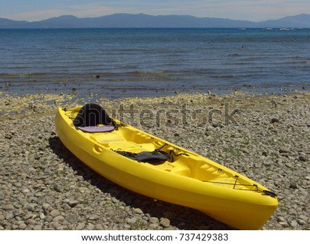 Bright yellow canoe beached on the shore of Lake Tahoe, CA on a summer day