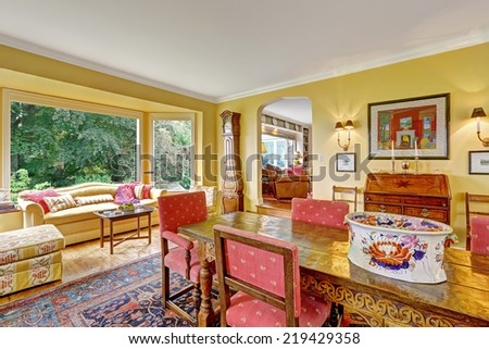 Bright yellow dining room with antique carved wood table and sitting area with wide window - stock photo