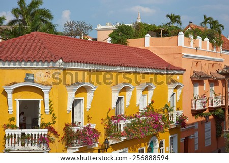 Bright yellow facade covered in plants and flowers in the historic UNESCO World Heritage Site of Cartagena de Indias in Colombia - stock photo